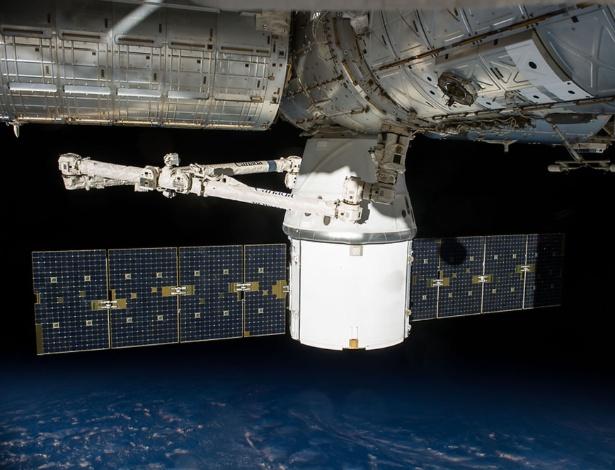 Cápsula Dragon, da empresa SpaceX, aparece acoplada à Estação Espacial Internacional (ISS, na sigla em inglês), para descarregar suprimentos e equipamento para os astronautas a bordo. A SpaceX tentará pela primeira vez pousar o foguete Falcon 9 na plataforma flutuante no oceano, após desacoplar a cápsula da ISS. As chances de sucesso são de 50%, segundo especialistas