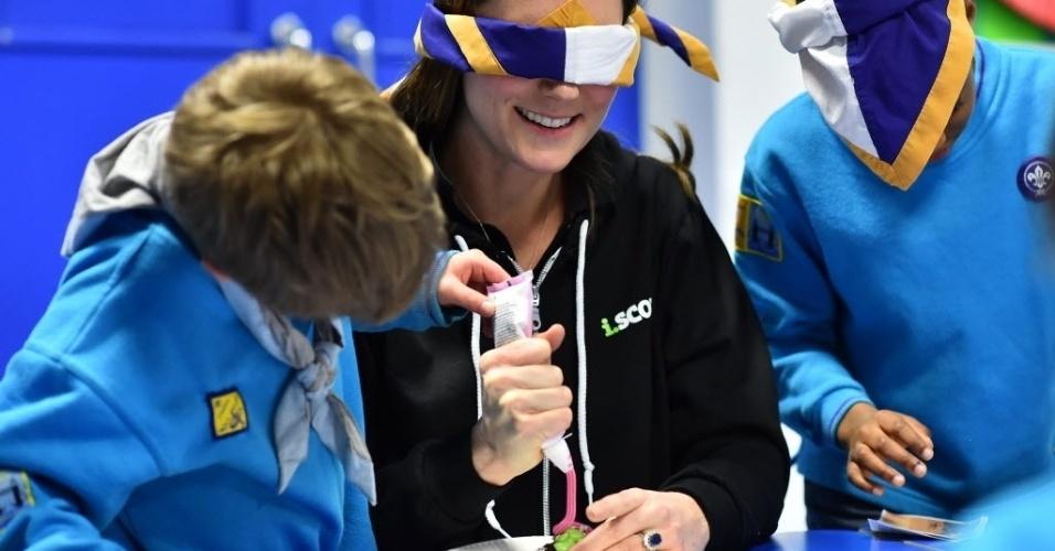17.dez.2014 - Kate Middleton, a duquesa de Cambridge (ao centro), vendou seus olhos nesta terça-feira (16) e recebeu ajuda de crianças para decorar um cupcake ao participar de um evento da Associação dos Escoteiros em Londres, na Inglaterra. A duquesa chamou atenção dos fotógrafos por ter abandonado seus vestidos da última moda para usar o moletom no evento