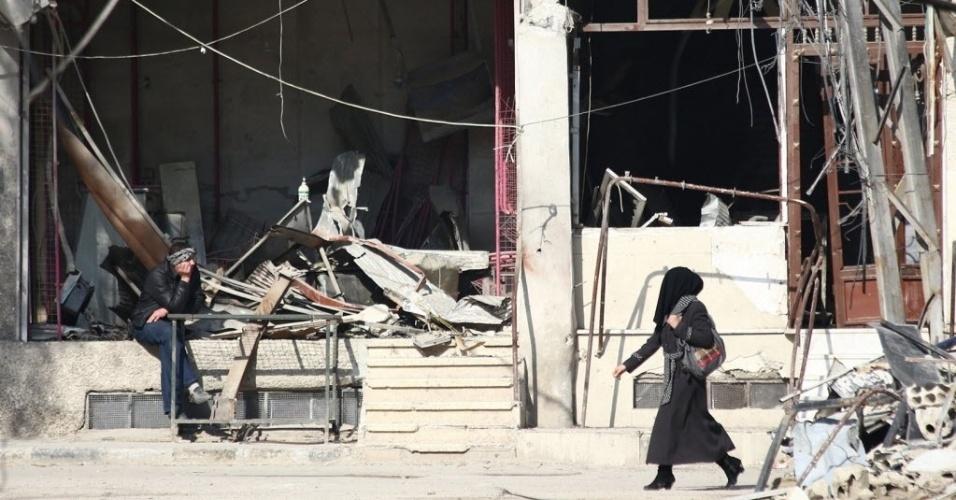 17.dez.2014 - Mulher síria caminha nesta quarta-feira (17) em frente a uma oficina destruída em Arbeen, uma cidade sob controle dos rebeldes na periferia de Damasco, na Síria. Grande parte do país tem sido devastada pela guerra contra o regime do ditador Bashar al Assad, em curso desde março de 2011, deixando mais de 200 mil mortos