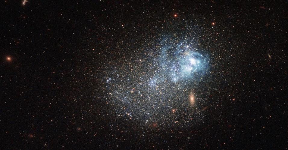 """19.dez.2014 - Este """"glitter cósmico"""" é uma galáxia anã compacta e azul conhecida como Markarian 209. A imagem foi feita pelas Wide Field Camera 3 e Advanced Camera for Surveys, do telescópio espacial Hubble. Galáxias desse tipo possuem tons de azul e são de tamanho compacto, ricas e gás e pobres em elementos pesados. Esses elementos são frequentemente estudados pelos astrônomos nas investigações sobre a formação das estrelas, pois supostamente possuem condições semelhantes com as da origem do universo. Markarian 209 ainda é muito jovem, em termos estelares, e tem até 3 milhões de anos. Para efeito de comparação, o sol tem cerca de 4,6 bilhões de anos"""