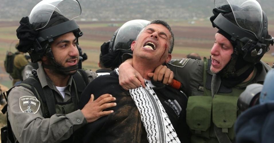 19.dez.2014 - Guardas da fronteira israelense prendem um manifestante palestino durante confrontos após protesto contra os assentamentos israelenses na aldeia de Turmus Aya, na Cisjordânia