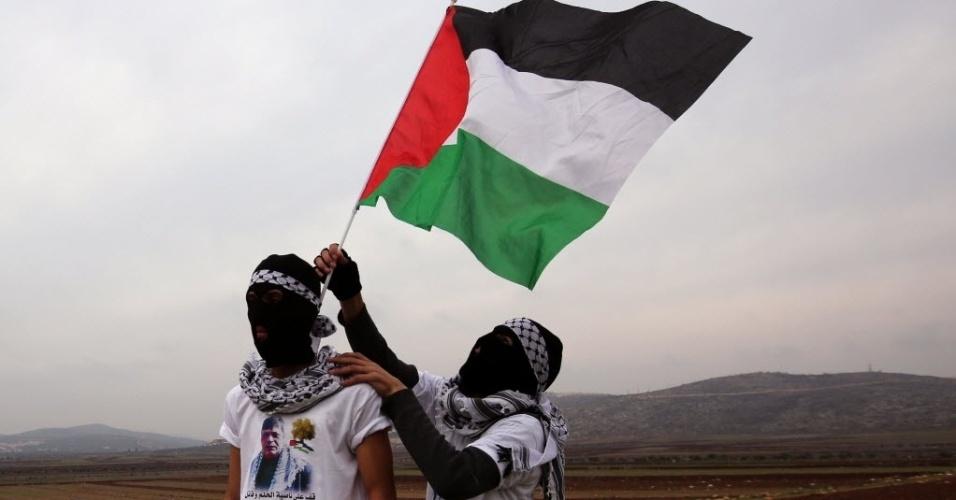 19.dez.2014 - Manifestantes palestinos seguram uma bandeira nacional e vestem camisetas com o retrato de Ziad Abu Ein, um alto funcionário palestino que morreu no início deste mês em um confronto com tropas israelenses, durante um protesto contra os assentamentos na aldeia Turmus Aya, na da Cisjordânia
