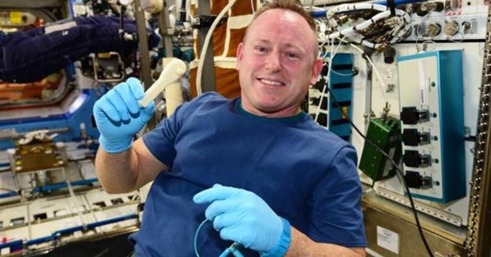 20.dez.2014 - O comandante da ISS (Estação Espacial Internacional), Butch Wilmore, exibe uma ferramenta fabricada com uma impressora 3D. Depois de receber um e-mail enviado da Terra, os astronautas usaram a impressora para fabricar uma espécie de chave inglesa, com desenho transmitido pela internet. Esta foi a primeira vez em que os tripulantes da estação orbital conseguiram construir uma ferramenta que faltava usando a impressora 3D, fabricada especialmente para espaços sem gravidade. A chave foi desenhada pela empresa Made in Space, com sede na Califórnia, que também fabricou a impressora