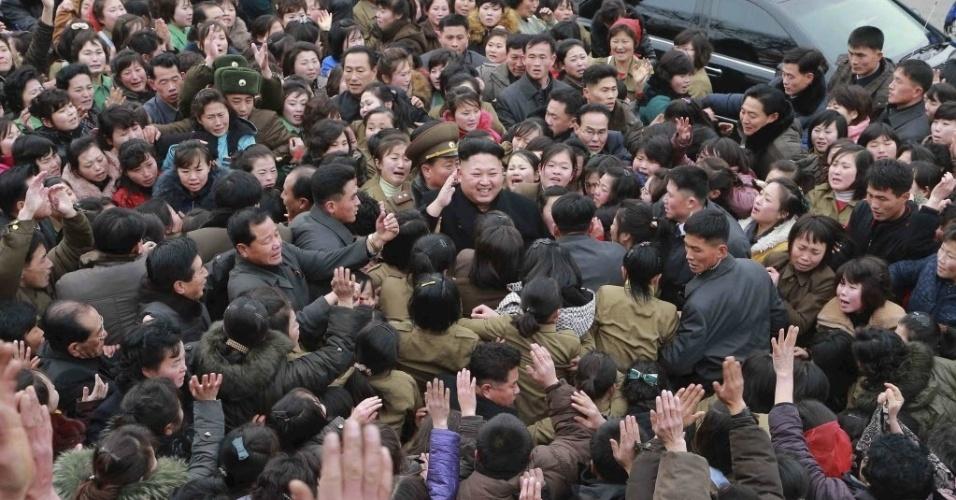 20.dez.2014 - O ditador norte-coreano Kim Jong Un sorri enquanto uma multidão o rodeia durante visita a uma fábrica têxtil em Pyongyang. A foto, sem data definida, foi divulgada pela Agência de Notícias da Coreia do Norte neste sábado (20). A aparição do ditador ocorreu em meio a uma polêmica envolvendo um ciberataque contra a Sony, o qual os Estados Unidos culpam a Coreia do Norte