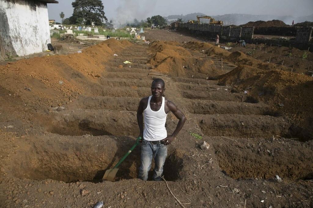 21.dez.2014 - Coveiro prepara novos túmulos em um cemitério em Freetown, em Serra Leoa, neste domingo (21). Cerca de 40 vítimas de ebola estão sendo enterradas neste cemitério todos os dias, enquanto o país continua a lutar contra a epidemia