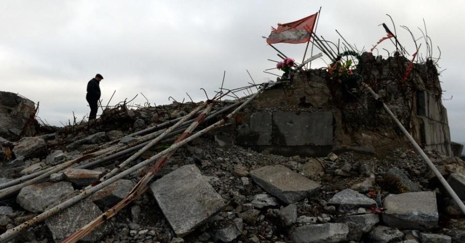 21.dez.2014 - Homem caminha neste domingo (21) entre os destroços do memorial