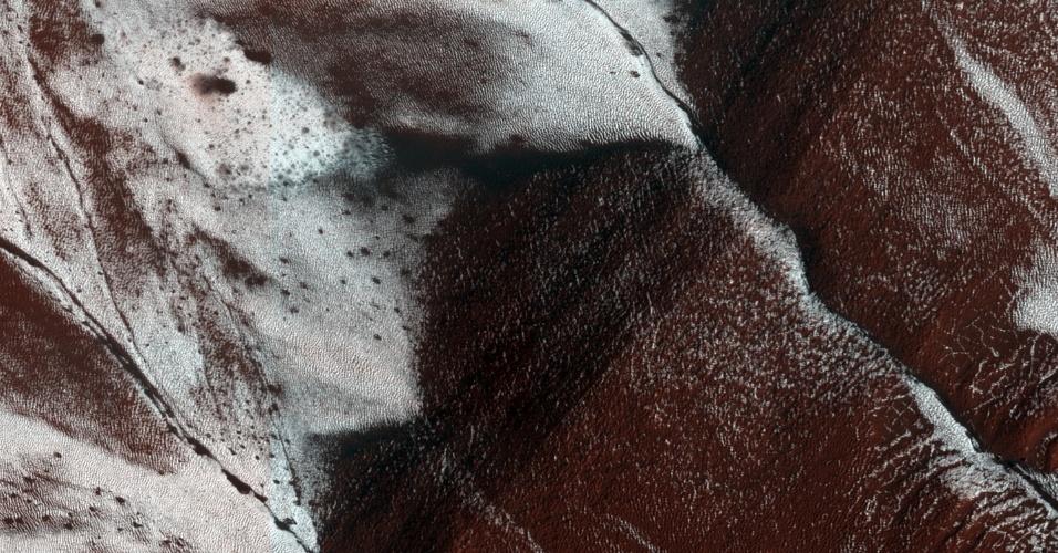 23.dez.2014 - Em imagem da superfície de Marte, que mostra cerca de 1,5 km por 3 km do solo, os cientistas conseguiram identificar um barranco congelado em uma encosta ao sul do planeta. A fotografia foi capturada no dia 30 de novembro pela câmera de alta resolução Imaging Science Experiment, da Nasa (Agência Espacial Americana). Nesta época do ano, apenas a face sul do planeta apresenta trilhas congeladas, enquanto as encostas voltadas para o norte já derreteram