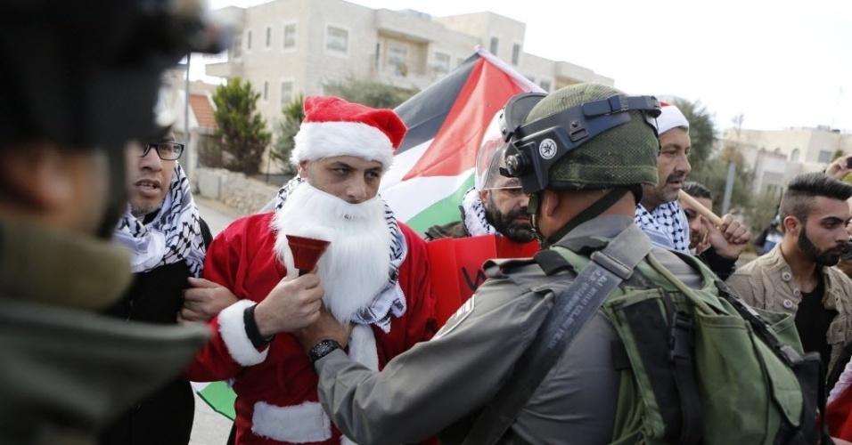 23.dez.2014 - Vestido de Papai Noel, palestino protesta contra os contra os assentamentos israelenses e exige livre circulação durante o Natal, perto de um posto de controle na cidade de Belém, na Cisjordânia