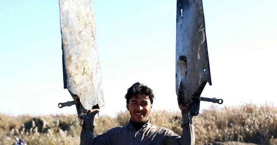 24.dez.2014 - Imagem divulgada em sites jihadistas mostra um combatente do Estado Islâmico exibindo peças de um avião militar da coalizão internacional que teria sido abatido com um míssil antiaéreo pelo grupo na cidade de Al Raqqah, na Síria