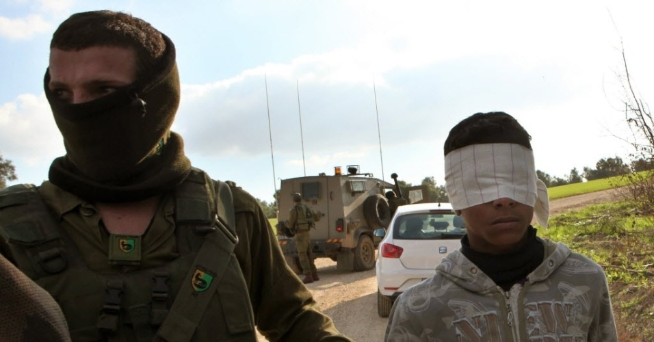 24.dez.2014 - Um soldado israelense detém um adolescente palestino na fronteira entre Israel e a faixa de Gaza