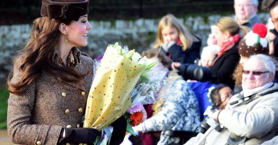 25.dez.2014 - Kate Middleton, a duquesa de Cambridge, recebe nesta quinta-feira (25) flores de britânicos após participar com os outros membros da família real de um tradicional evento de Natal na igreja em Sandringham, ao leste da Inglaterra