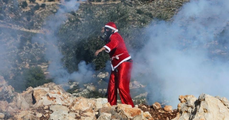26.dez.2014 - Manifestante palestino vestido de Papai Noel lança uma lata de gás lacrimogêneo contra soldados israelenses durante confrontos na aldeia de Bilin, a oeste de Ramallah. O confronto ocorreu após uma marcha organizada em solidariedade ao povo da aldeia Maasara, que protestou pela construção de assentamentos e contra o confisco de terras