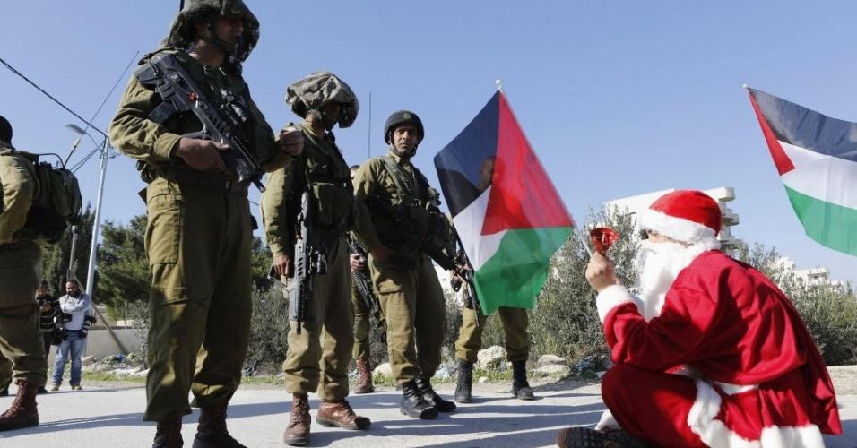 26.dez.2014 - Manifestante palestino vestido de Papai Noel senta na frente de soldados israelenses durante um protesto pela construção de assentamentos na aldeia Maasara, perto da cidade de Belém, na Cisjordânia
