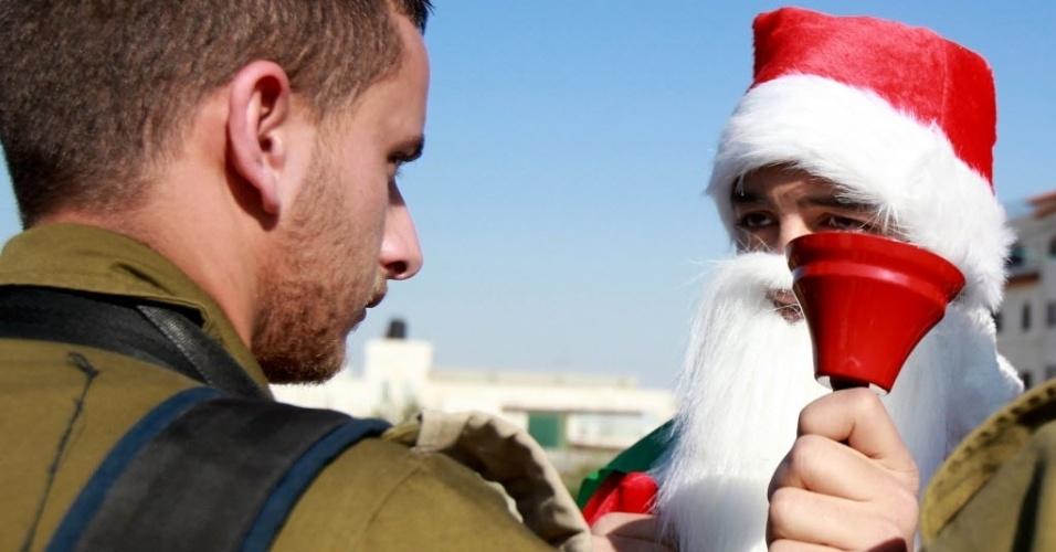 26.dez.2014 - Manifestante palestino vestido de Papai Noel toca sino perto de um soldado israelense durante uma manifestação pela construção de assentamentos e contra o confisco de terras, na aldeia de Maasarah, perto de Belém, na Cisjordânia