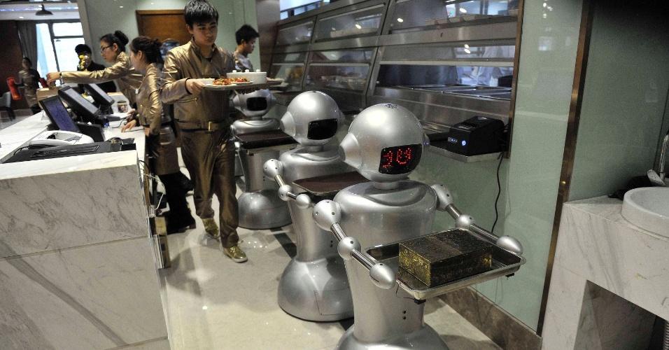 26.dez.2014 - Um homem coloca refeições na bandeja de robôs em um restaurante na cidade de Hefei, na província de Anhui (China). O restaurante, que tem uma área de 1.300 metros quadrados, conta com 30 robôs que recepcionam os clientes, cozinham e ainda entregam as refeições aos consumidores. O estabelecimento é o maior do tipo em atividade no país