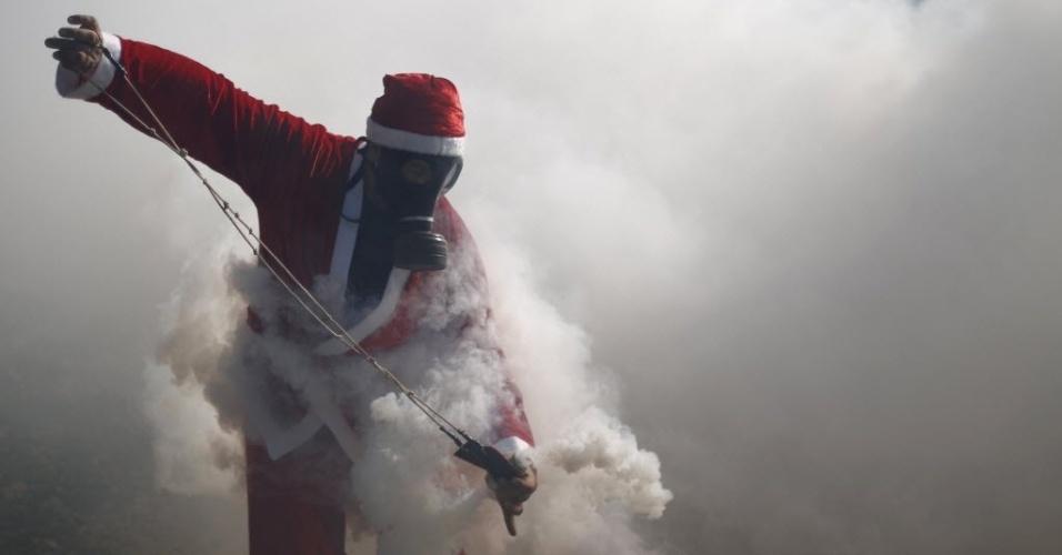 26.dez.2014 - Um manifestante palestino, vestido como Papai Noel, usa um estilingue para devolver uma bomba de gás lacrimogêneo disparada por soldados israelenses durante um protesto na cidade de Ramallah