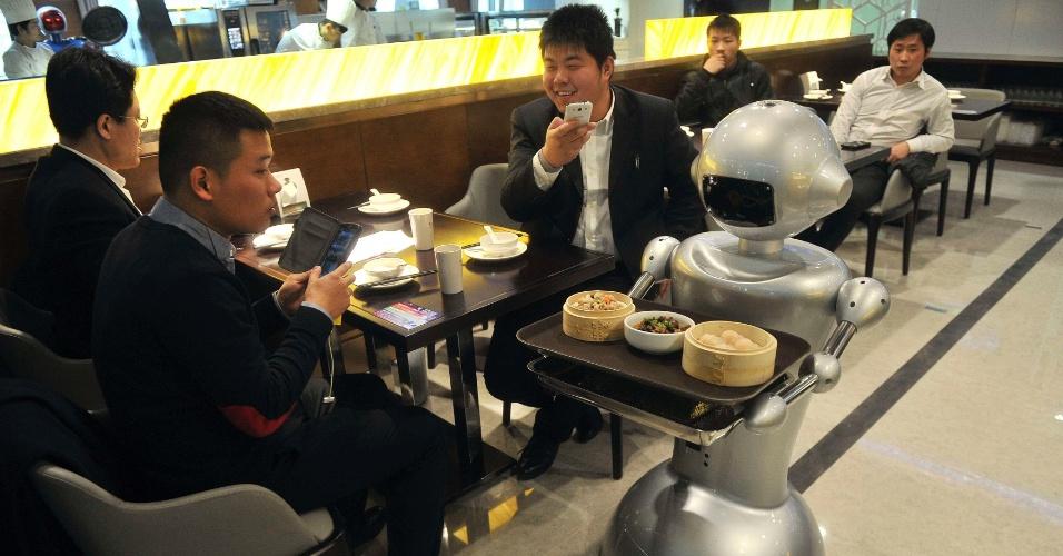 26.dez.214 - Robô entrega refeição a um cliente em um restaurante na cidade de Hefei, província de Anhui (China). O restaurante, que tem 1.300 metros quadrados, é considerado o maior do estabelecimento do tipo no país. Ao todo, são 30 robôs que recepcionam os clientes, cozinham e ainda entregam os pedidos aos consumidores