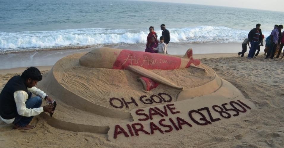 28.dez.2014 - Artista Sudarshan Pattnaik faz escultura de areia na praia de Gopalpur, na Índia, em homenagem ao voo QZ8501 da companhia aérea AirAsia que desapareceu na Ásia neste domingo (28)