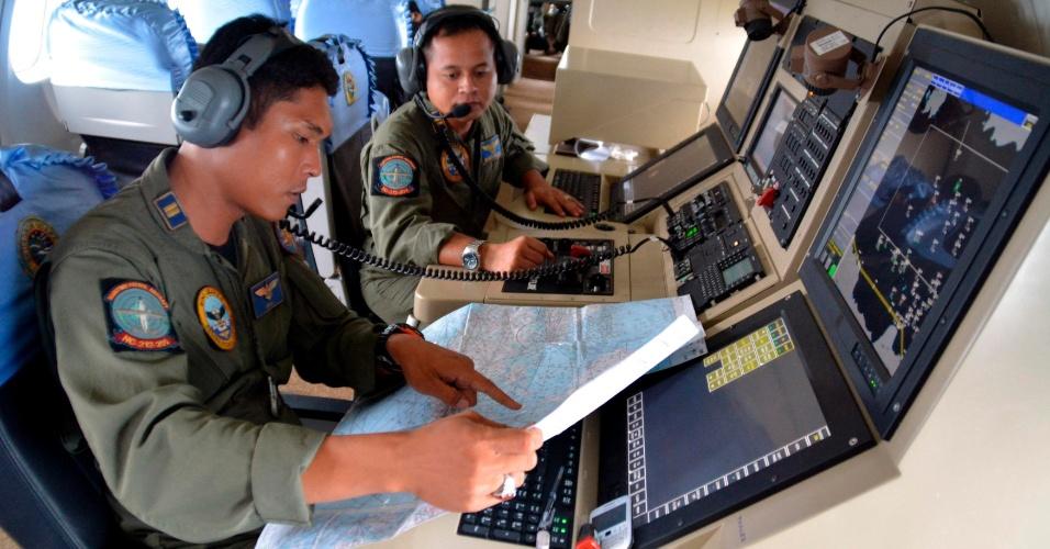 28.dez.2014 - Em uma aeronave de patrulha, dois integrantes da Marinha da Indonésia ajudam nas buscas pelo avião desaparecido da AirAsia. Na manhã deste domingo (28), a aeronave, que transportava 162 passageiros do voo QZ 8501, perdeu contato com a torre de controle cerca de 40 minutos após decolar