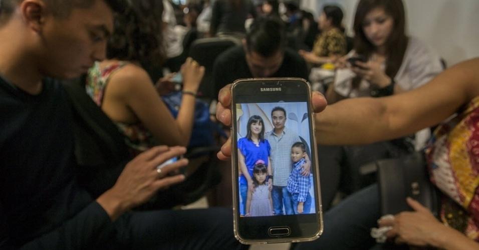 28.dez.2014 - Familiar mostra uma imagem de supostos passageiros que viajavam voo QZ8501 da companhia aérea AirAsia, no aeroporto de Surabaya, em Java Oriental. O avião com 162 pessoas a bordo desapareceu quando ia da Indonésia para Cingapura