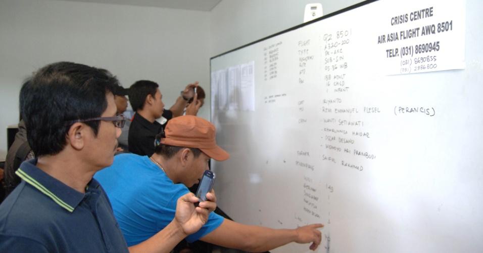 28.dez.2014 - Familiares observam quadro com informações sobre a aeronave desaparecida da AirAsia no Aeroporto Internacional de Juanda, na Indonésia, de onde partiu o voo QZ 8501 na manhã deste domingo (28), hora local, com destino a Cingapura. No total, 162 pessoas estavam a bordo do avião, que desapareceu 40 minutos após a decolagem