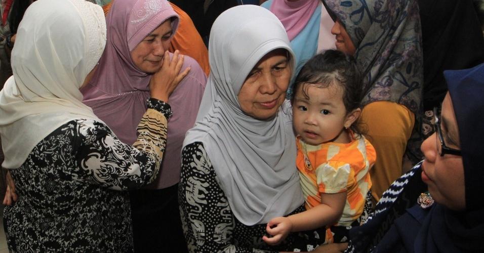 28.dez.2014 - Mãe de aeromoça do voo QZ 8501 recebe familiares em sua casa em Palembang, no sul da ilha de Sumatra, na Indonésia. Ela acompanha as notícias sobre a operação de busca pelo avião desaparecido da AirAsia. Sua filha é uma das 162 pessoas a bordo da aeronave, que tinha Cingapura como destino