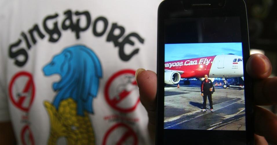 28.dez.2014 - Parente de passageiro mostra foto que o familiar teria tirado antes de embarcar no avião da AirAsia, que desapareceu entre Indonésia e Cingapura na manhã deste domingo (28). O avião transportava 162 pessoas, entre passageiros e tripulantes