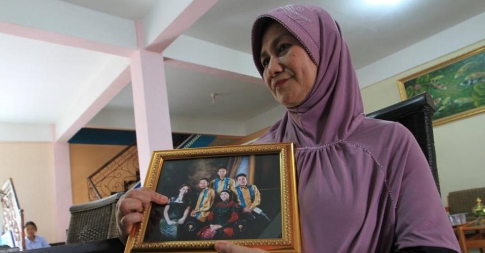28.dez.2014 - Rohana, mãe de Khairunisa, comissária de bordo que estava viajando no voo QZ8501 da companhia aérea AirAsia, aponta para sua filha em uma fotografia da família em Palembang, em Sumatra. As equipes de resgate vasculharam o mar de Java em busca do avião que transportava 162 pessoas da Indonésia para Cingapura