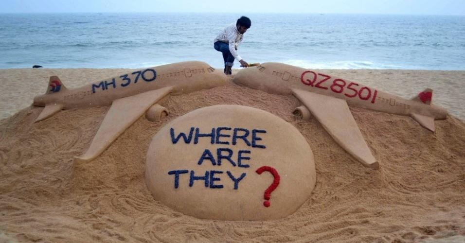 29.dez.2014 - Artista Sudarshan Pattnaik finaliza escultura de areia na praia de Golden Sea, na Índia, em homenagem aos voos QZ8501, da AirAsia, e MH370, da Malayasia Airlines, que desapareceram na Ásia