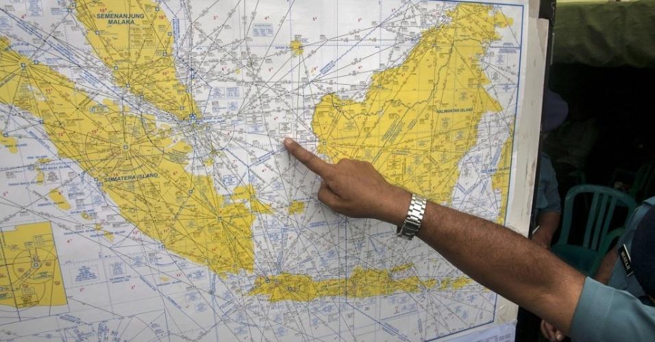 29.dez.2014 - Integrante da equipe da Força Aérea da Indonésia aponta local das buscas pelos passageiros do voo QZ8501 da AirAsia, que perdeu contato com o controle aéreo, no estreito de Karimata, na Indonésia. O avião com 162 pessoas a bordo desapareceu ao fazer a tora da Indonésia até Cingapura neste domingo (28), de acordo com a companhia aérea. Este é o terceiro grande incidente envolvendo uma companhia malaia neste ano