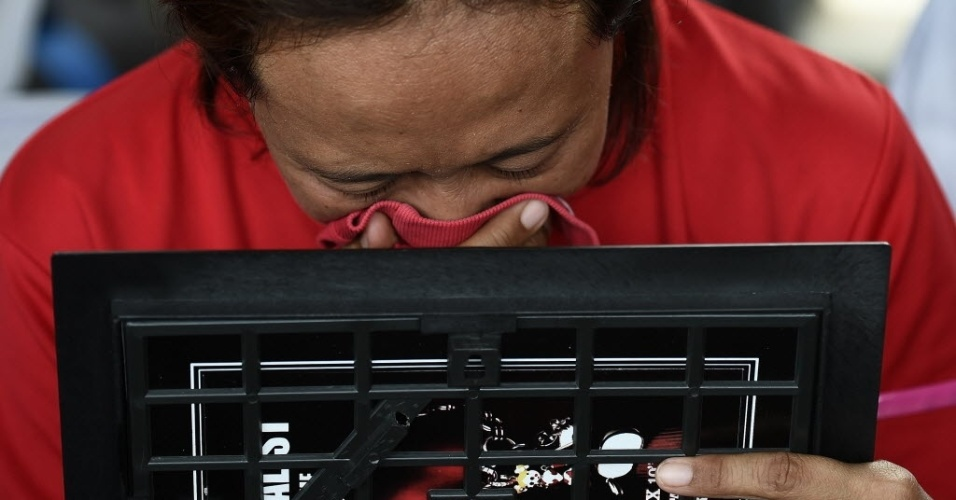 29.dez.2014 - Mulher chora ao observar foto de familiares que estavam a bordo do voo QZ 8501 da AirAsia, nesta segunda-feira (29), no aeroporto internacional de Juanda, na Indonésia. O avião com 162 pessoas a bordo perdeu contato com a torre de comando em Jacarta, na Indonésia, cerca de 40 minutos após a decolagem. Este é o terceiro grande incidente envolvendo uma companhia malaia neste ano