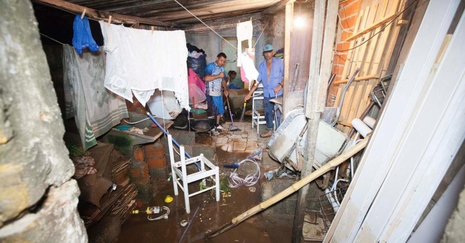 30.dez.2014 - Moradores de casa no Itaim Paulista, zona leste de São Paulo, limpam sujeira deixada por alagamento provocado pelo transbordamento de córrego após a chuva que atingiu a região na tarde de segunda-feira (29)