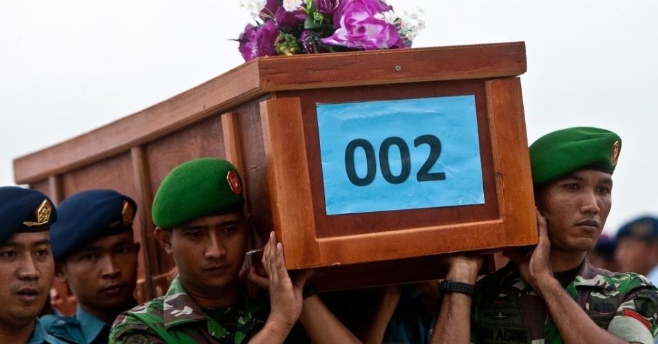 31.dez.2014 - Militares carregam caixão de vítima do voo QZ8501 da AirAsia, que chegou na base militar de Surabaia, na Indonésia, após corpo ter sido resgatado no mar de Java. As buscas por corpos das 162 pessoas que estavam a bordo do avião que caiu no domingo (28) foram prejudicadas nesta quarta-feira (31) devido ao mau tempo
