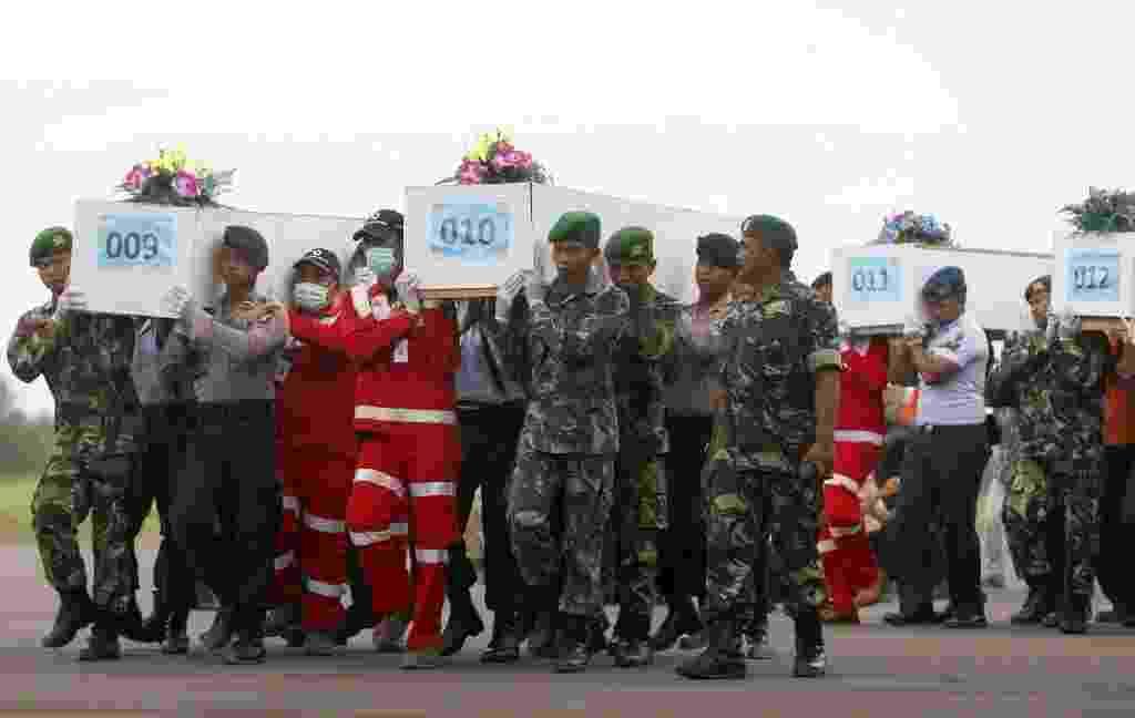 2.jan.2015 - Caixões com restos mortais de vítimas do voo QZ8501 da AirAsia resgatados do mar de Java são carregados para avião militar, em aeroporto de Kalimantan, antes de serem levados para Surabaya, na Indonésia. As equipes de busca do avião ganharam o reforço de investigadores franceses e de mergulhadores - Darren Whiteside/Reuters