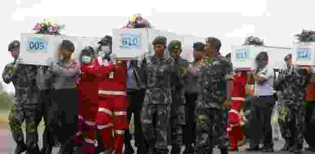 Caixões com restos mortais de vítimas do voo QZ8501 da AirAsia, resgatados do mar de Java, são carregados para avião militar em aeroporto de Kalimantan - Darren Whiteside/Reuters - 2.jan.2015