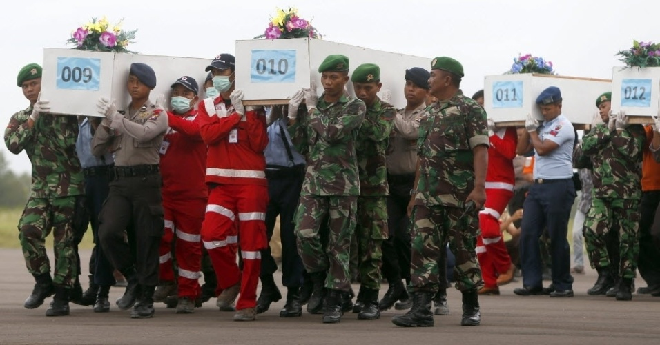 2.jan.2015 - Caixões com restos mortais de vítimas do voo QZ8501 da AirAsia resgatados do mar de Java são carregados para avião militar, em aeroporto de Kalimantan, antes de serem levados para Surabaya, na Indonésia. As equipes de busca do avião ganharam o reforço de investigadores franceses e de mergulhadores