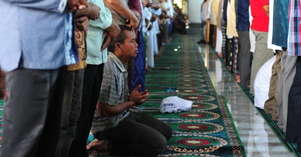 2.jan.2015 - Homem fica de joelhos durante oração em memória das vítimas do voo QZ8501 da AirAsia na mesquita Al-Akbar, em Surabaya, na Indonésia. O avião caiu com 162 pessoas a bordo no mar de Java, no dia 28 de dezembro de 2014