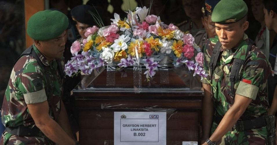 2.jan.2015 - Militares carregam caixão de Grayson Herbert Linaksita, vítima do voo QZ8501 da AirAsia, que caiu no mar de Java, na Indonésia, com 162 pessoas a bordo. As equipes de busca do avião esperavam conquistar avanços importantes na busca por corpos com a participação de investigadores franceses e o início das buscas submarinas