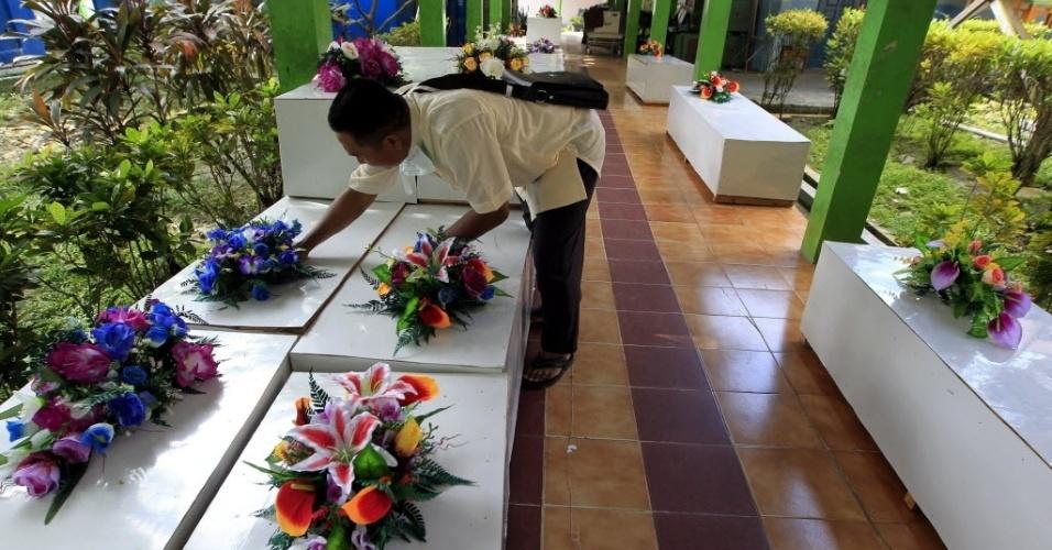 2.jan.2015 - Homem arruma flores sobre caixões que serão usados para transportar os corpos de vítimas do voo QZ8501 da AirAsia que forem encontrados no mar de Java, na Indonésia. Nesta sexta-feira (2), as equipes de resgate encontraram 19 corpos, levando a 30 o total