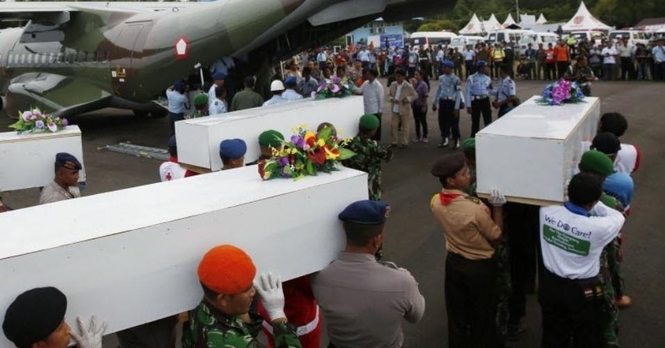 2.jan.2015 - Soldados do exército da Indonésia transportam caixões com corpos de vítimas do voo QZ8501 da AirAsia no aeroporto de Iskandar, em Pangkalan Bun, antes de translado para Surabaya, na Indonésia. Especialistas franceses do Escritório de Investigação e Análise (BEA) para a segurança da aviação civil reforçam a equipe com hidrofones para detectar sinais das caixas-pretas
