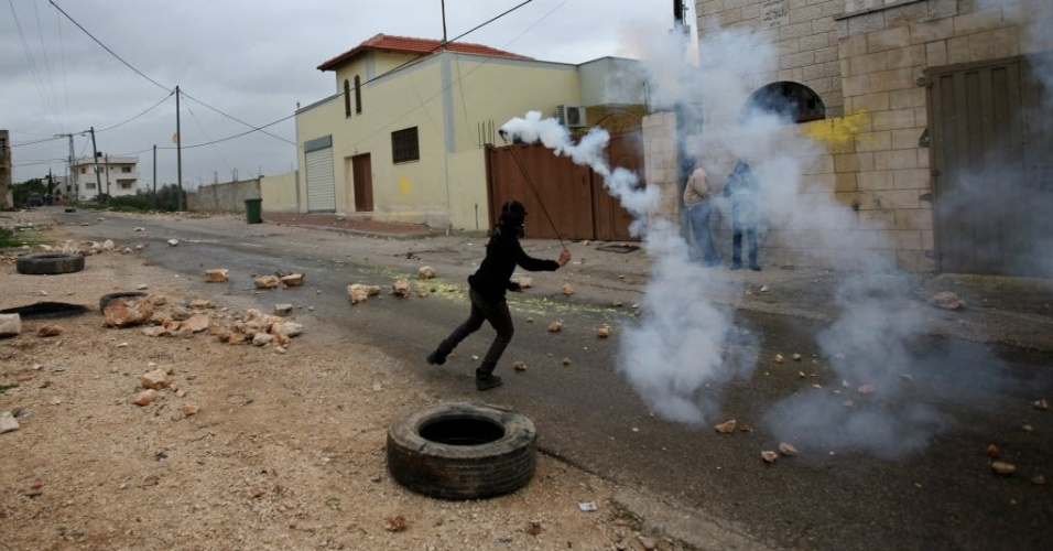 2.jan.2015 - Manifestante palestino devolve bomba de gás lacrimogêneo arremessada por soldados israelenses, nesta sexta-feira (2), durante protesto contra a expansão de assentamentos judaicos na vila de Kufr Qadoom, perto da cidade de Nablus, na Cisjordânia