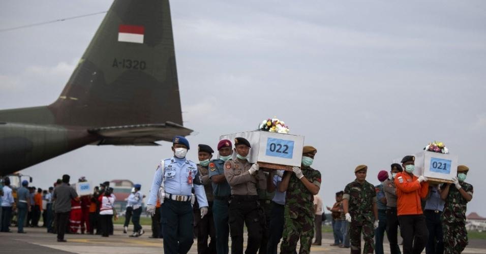 3.jan.2015 - Militares indonésios transportam caixões com os restos mortais de passageiros a bordo do voo QZ8501 AirAsia, que caiu e foi encontrado na costa de Bornéu. O avião tinha 162 pessoas a bordo. Equipes de buscas retomaram uma operação de resgate dos corpos neste sábado (3)