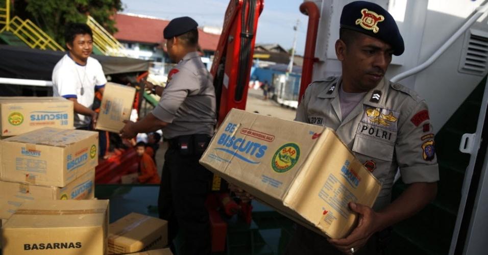 3.jan.2015 - Policiais da Indonésia carregam caixas de comida para navio usado em operação de busca dos corpos dos passageiros do voo da AirAsia, que caiu no Mar de Java. Não há sobreviventes do acidente