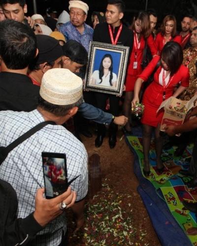 3.jan.2015 - Familiares e amigos rezam no enterro de Khairunisa, uma das comissárias de bordo que estava no voo QZ8501 da AirAsia, neste sábado (3), em Palembang, na Indonésia. Autoridades indonésias esperam esclarecer a causa do acidente que causou a morte de 162 pessoas