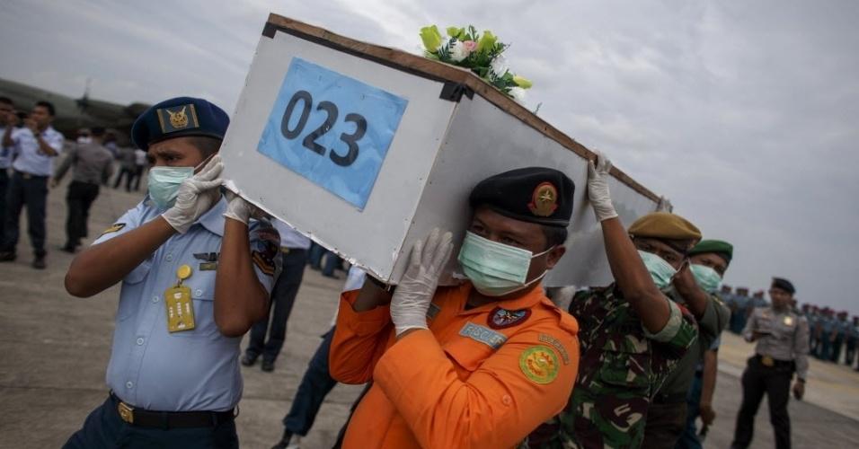 3.jan.2015 - Militares carregam caixão de vítima do voo QZ8501 da AirAsia, que chegou na base militar de Surabaia, na Indonésia, após corpo ter sido resgatado no mar de Java. Autoridades indonésias esperam esclarecer a causa do acidente que causou a morte de 162 pessoas