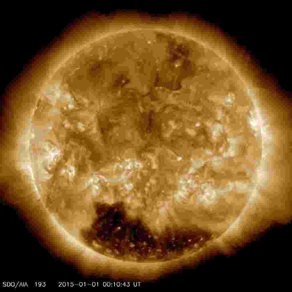 3.jan.2015 - Não houve fogos de artifício no Sol para receber o Ano-Novo. No entanto, o astro começou 2015 com um enorme buraco coronal (região mais escura e de baixa densidade) perto do polo Sul. O fenômeno foi observado por um instrumento do Observatório de Dinâmica Solar da Nasa (agência espacial americana). A agência explica que esse tipo de buraco fica localizado em uma região da camada mais externa do Sol, conhecida como corona, em que o campo magnético se estende para o espaço em vez de ficar contido na superfície solar. As partículas que se deslocam nesses campos magnéticos podem, portanto, deixar o Sol em vez de ficarem presas em sua superfície - NASA/SDO/Divulgação