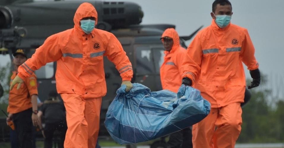 4.jan.2015 - Membros da equipe de resgate da Indonésias carregam destroços do voo QZ8501 da AirAsia deixados em Pangkalan Bun, cidade do sul de Bornéu, por um helicóptero da força aérea de Singapura, neste domingo (4). Mergulhadores tentaram continuar o trabalho de buscas do AirAsia que caiu no domingo passado, mas foram obrigados a regressar ao seu navio diante do mau tempo, enquanto que autoridades indonésias disseram ter detectado um quinto grande objeto submerso que acredita-se ser parte do avião