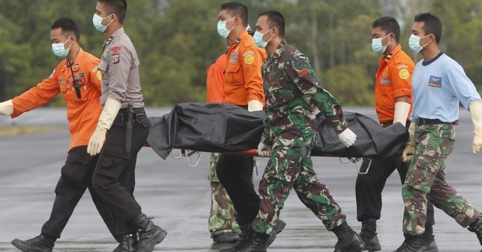 5.jan.2015 - Equipes de resgate transportam corpo de vítima do voo QZ8501 da AirAsia resgatado do mar de Java no aeroporto militar de Pangkalan Bun, no Bornéu, na Indonésia. Autoridades ampliaram a área de busca para encontrar os corpos das vítimas e os destroços do avião, que podem ter sido arrastados pelas correntes durante o período em que os trabalhos estiveram interrompidos pelo mau tempo. Até agora 34 cadáveres foram resgatados de um total de 162 pessoas que estavam a bordo da aeronave - 155 indonésios, o copiloto francês, um britânico, três sul-coreanos, um cingapuriano e um malaio