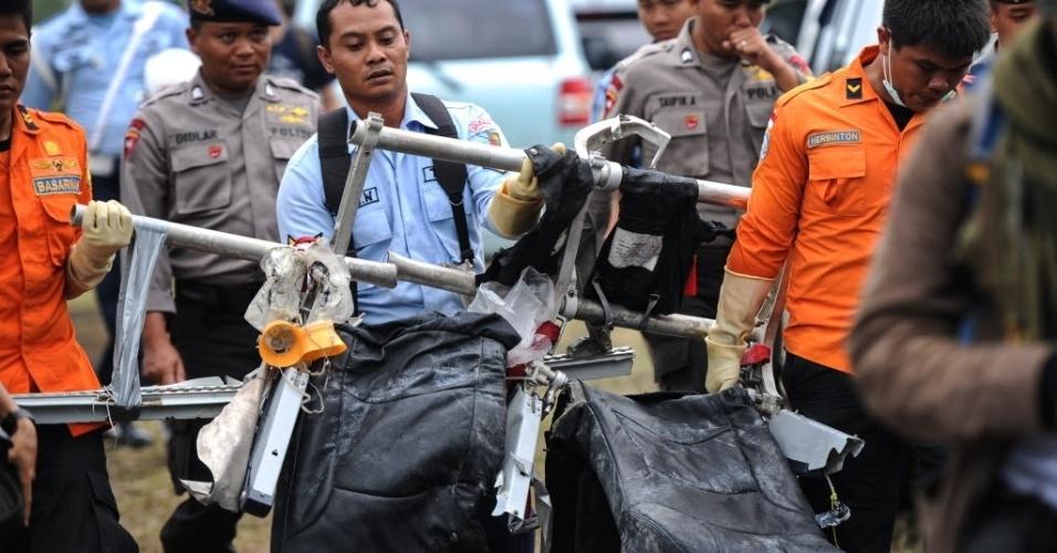 5.jan.2015 - Integrantes de equipe de resgate carregam destroços do voo QZ8501 da AirAsia trazidos de helicóptero do mar de Java, onde foram encontrados, para o aeroporto militar de Pangkalan Bun, no Bornéu, na Indonésia. Autoridades ampliaram a área de busca para encontrar os corpos das vítimas e os destroços do avião, que podem ter sido arrastados pelas correntes durante o período em que os trabalhos estiveram interrompidos pelo mau tempo