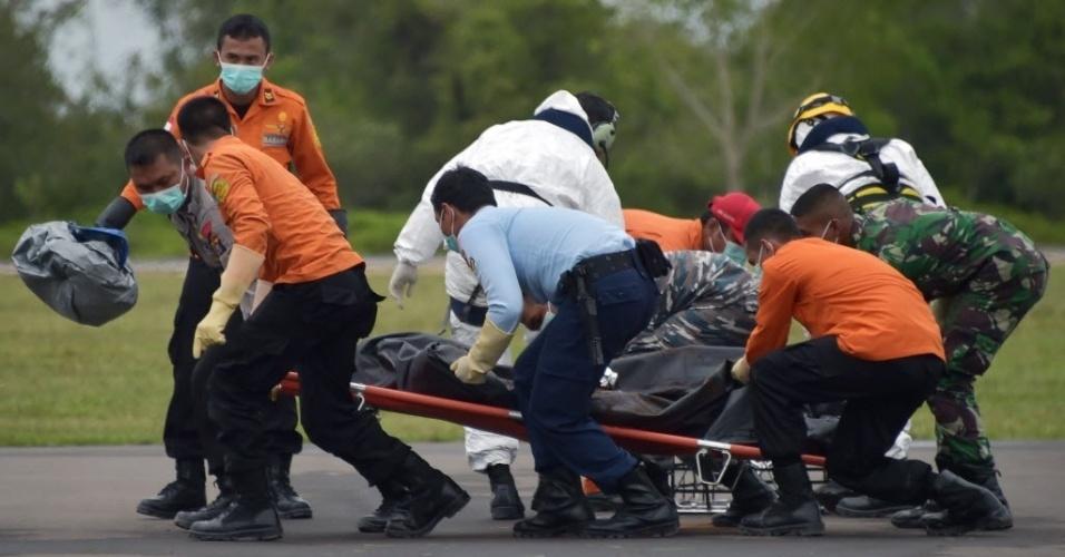 6.jan.2015 - Membros de uma equipe de resgate carregam corpo de passageiro do voo QZ8501 da AirAsia em Pangkalan Bun, cidade com a pista mais próxima do local das operações de busca, na Indonésia. Mergulhadores aproveitaram a melhora no tempo para intensificar as buscas por destroços e vítimas no mar de Java